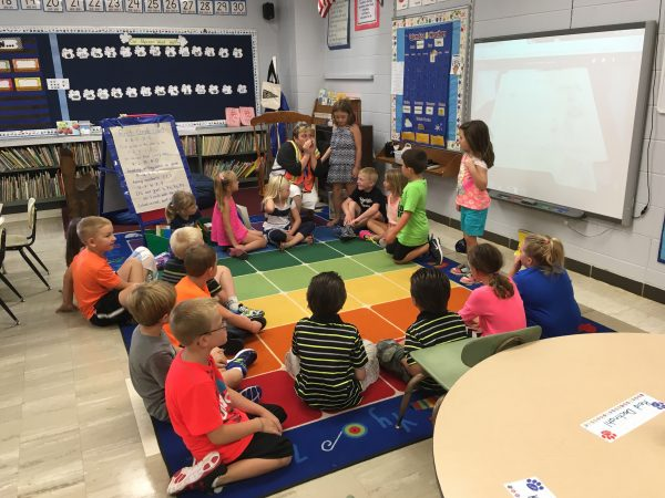 1st graders sit in a circle to get to know one another.